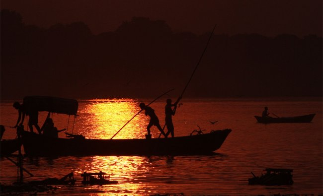 Boatmen make their way over the River Ganges during sunset in Allahabad on October 29, 2012...