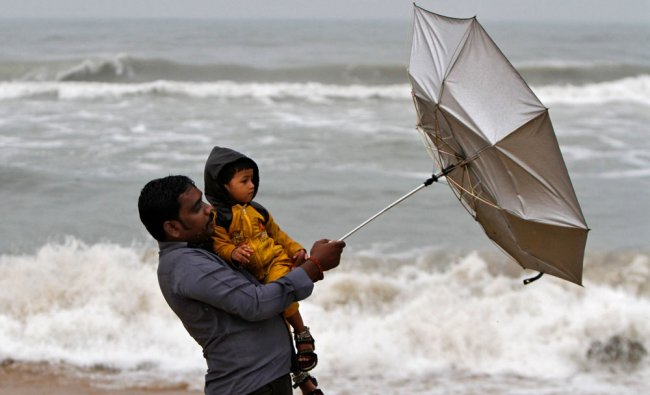 A man carrying his child tries to hold an umbrella at Marina beach