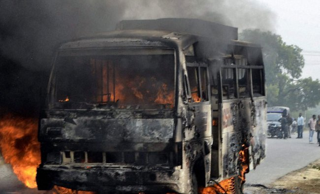A bus set on fire by a mob after death of a man in an accident in Unnao