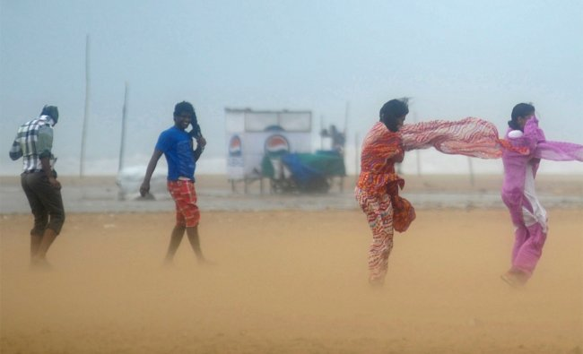 Women shield their faces during strong winds at Marina beach in Chennai...