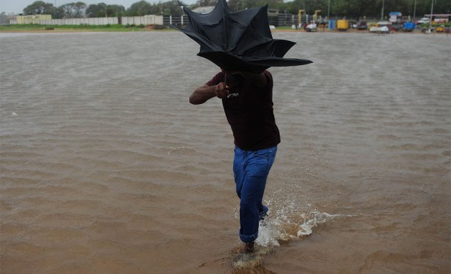 A man wades through a flooded area at Chennai in Tamil Nadu...
