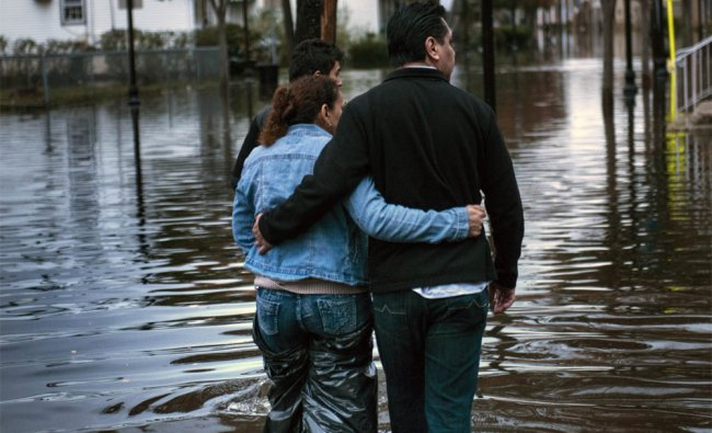 A family navigate their way home after flood waters receded to walkable levels in New York...
