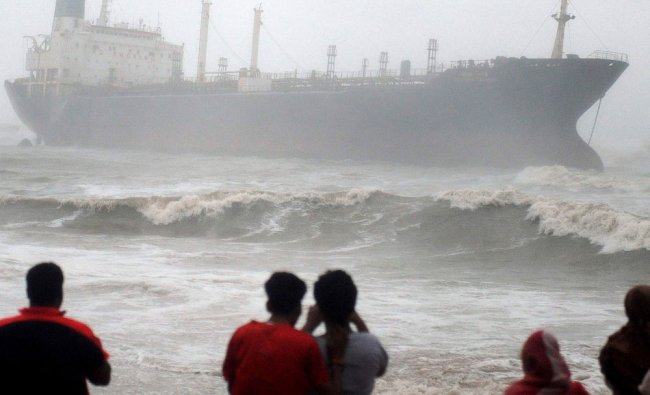Onlookers watch ship Pratibha Cauvery, which ran aground allegedly due to strong winds