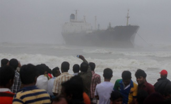 Onlookers gather on the beach after the oil tanker ship Pratibha Cauvery ran aground