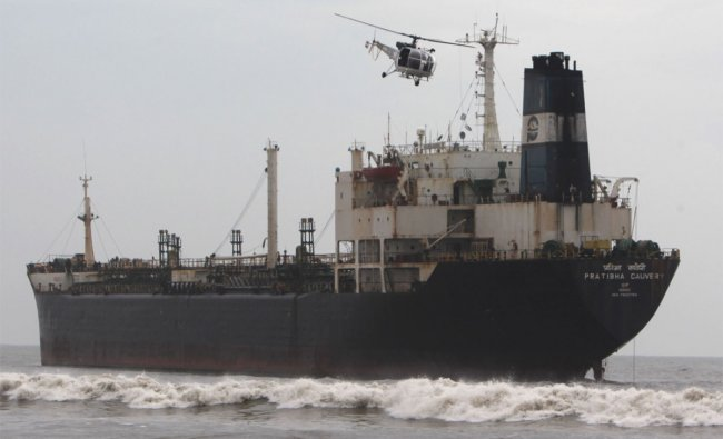 An Indian Coast Guard HAL Chetak helicopter flies over the oil tanker ship Pratibha Cauvery