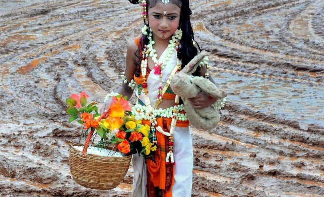 A child, dressed for Kannada Rajyothsava cultural programmes, walks in a mudddy field as the...