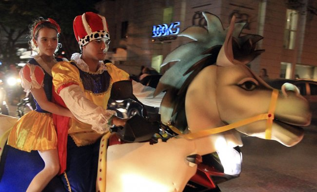 A couple rides on a motorbike, made to look like a donkey, during the \'Moto Halloween Party 2012...