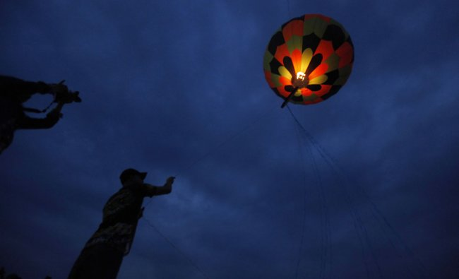 A man releases a paper balloon during a competition as part of the Day of the Dead celebrations in..