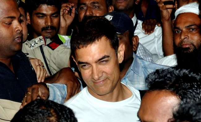 Bollywood actor Aamir Khan (C) smiles after returning from annual Hajj pilgrimage at the airport...