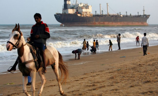 A man rides a horse past Indian ship Pratibha Cauvery which ran aground due to strong winds