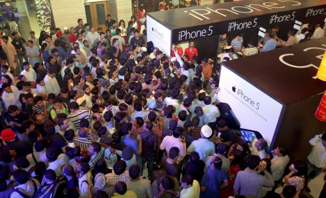 People crowd around an I-Phone store at a mall in Delhi, during the lauch of the I-Phone 5 in...