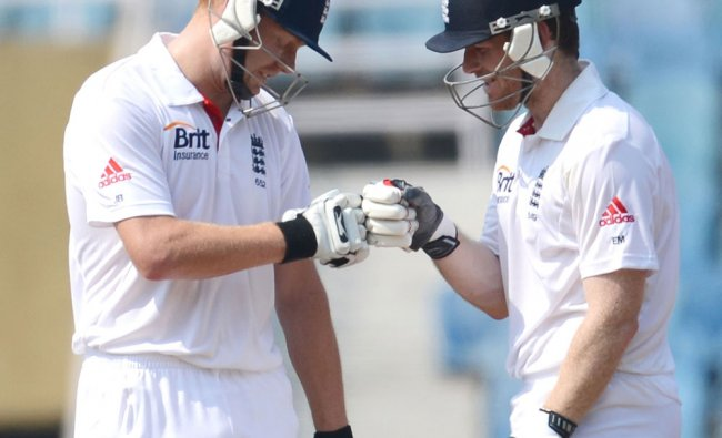 England cricketers Jonny Bairstow (L) and Eoin Morgan punch fists during the first day of a three...