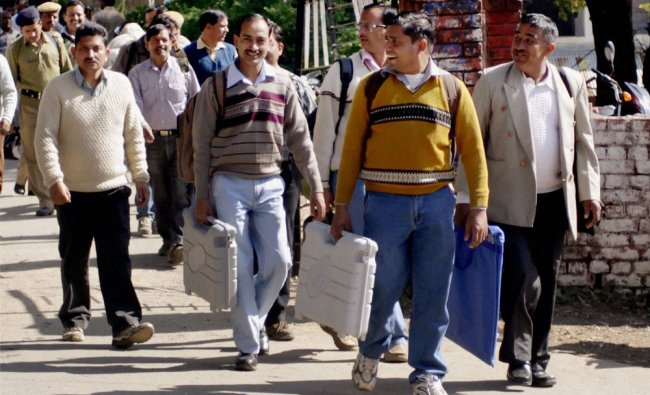 Election officials carrying EVM\'s from the distribution centre in Dharamshala ahead of November...