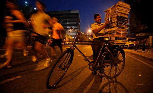 A newspaper vendor stacks newspapers on the carrier of his bicycle for distribution as people...