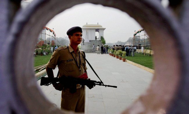 Security person stand guard on the eve of Congress party rally at Ramlila ground in New Delhi...