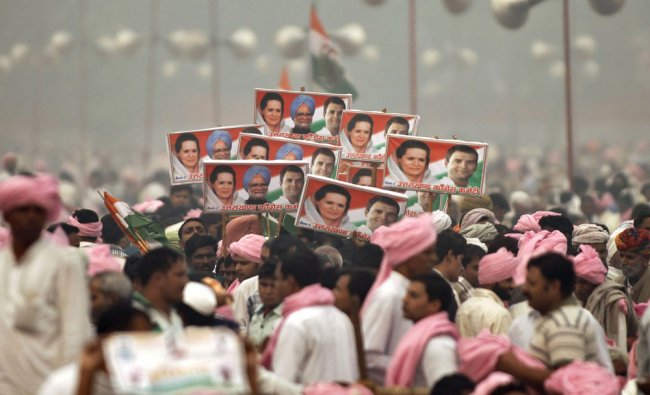 Congress party supporters hold posters during a public rally in Ramlila Maidan, New Delhi, on Sunday