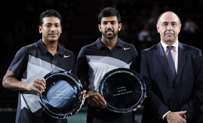 India\'s Rohan Bopanna (C) and teammate India\'s Mahesh Bhupathi (L) pose with their trophies near...