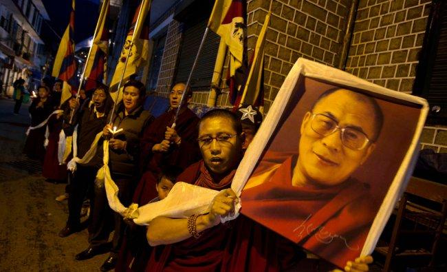 An exile Tibetan carries a portrait of the Tibetan spiritual leader the Dalai Lama during...