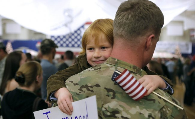 Gavin Shaw, 5, flashes a smile as he hugs his father, Master Sergeant Adam Shaw, during a Welcome...