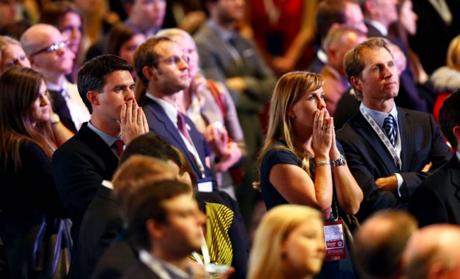 Spectators react to the election results displayed on large televisions during Mitt Romney\'s...