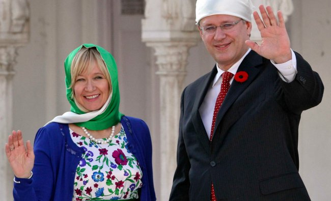 Canadian Prime Minister Stephen Harper (R) and his wife Laureen wave to the photographers...