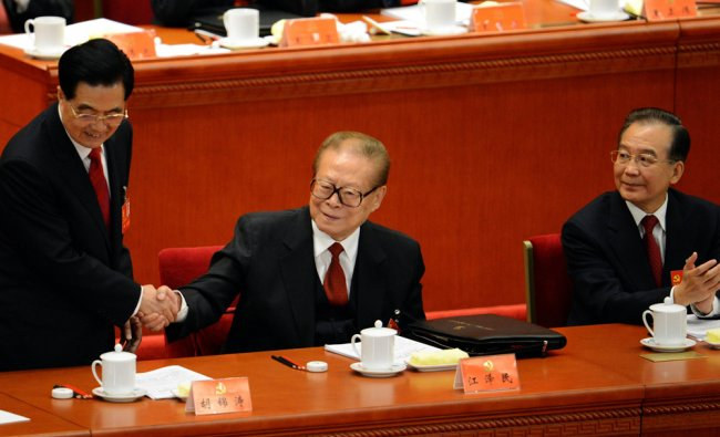 Chinese President Hu Jintao shakes hands with former president Jiang Zemin with Premier Wen Jiabao
