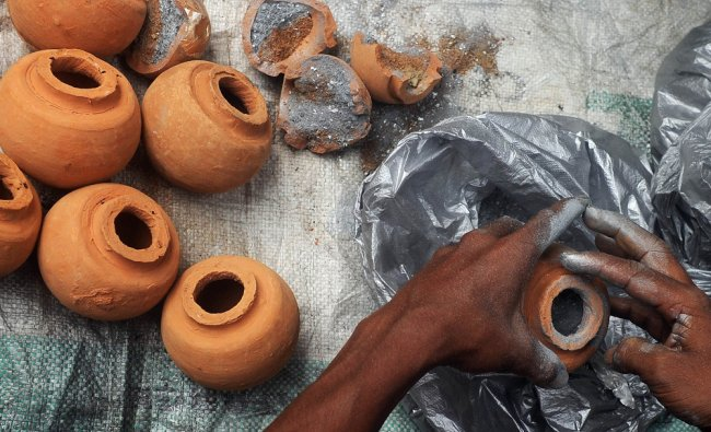 A worker puts gun powder inside a clay pot to make a fire crackers for the upcoming Diwali festival