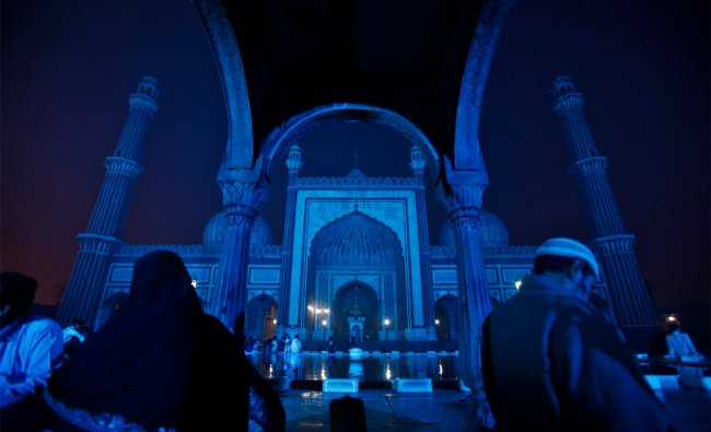 Muslims sit at the Jama Masjid (Grand Mosque), illuminated with blue lights