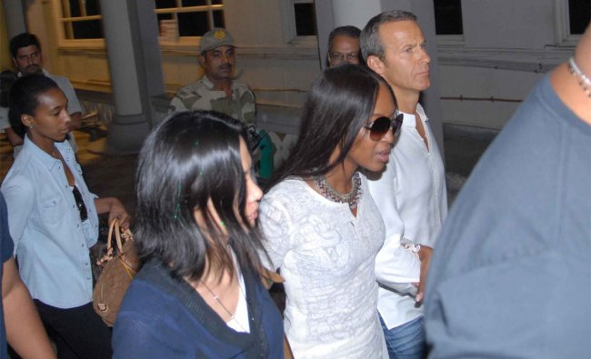 Naomi Campbell (2R) and her boyfriend Vladimir Doronin (R) walk with their security in Jodhpur