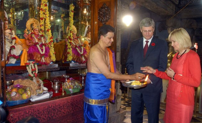 Canadian PM Stephen Harper (2R) and his wife Laureen Harper (R) get a blessing from a Hindu priest