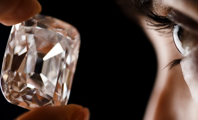 An employee poses with the Archduke Joseph diamond during an auction preview at Christie\'s