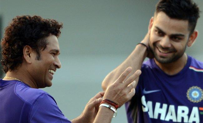 India cricketer Sachin Tendulkar shares a light moment with teammate Virat Kohli during a training..