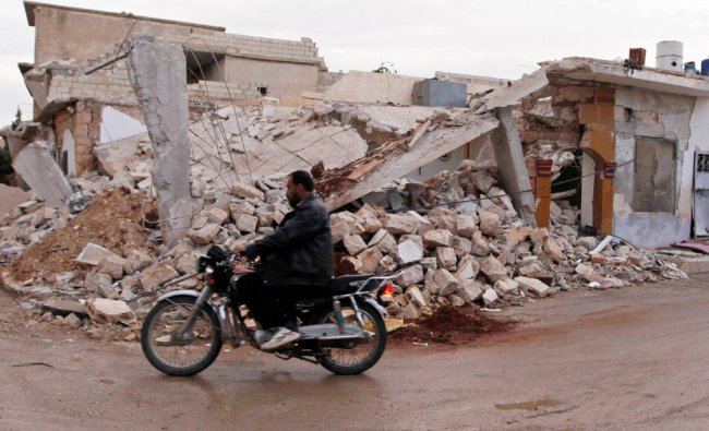 A civilian rides a motorcycle past a house damaged after shelling by forces