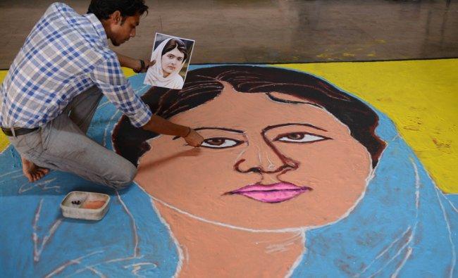 Art teacher, Ashish Jadav gives the finishing touches to a \'Malala Rangoli\' in Ahmedabad ...