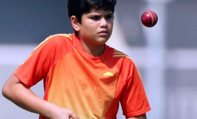 Sachin Tendulkar\'s son Arjun knocks the ball during Team India\'s practice session in Mumbai ...