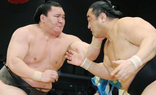 Yokozuna, or grand champion, Hakuho (L) of Mongolia pushes Japanese sumo wrestler Aminishiki