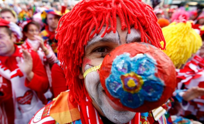 A carnival reveller dressed as clown poses at the start of the carnival in Cologne