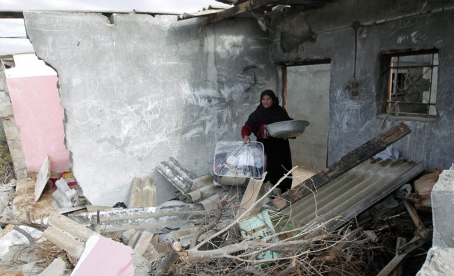 A Palestinian woman collects items from her destroyed home following an Israeli military air strike