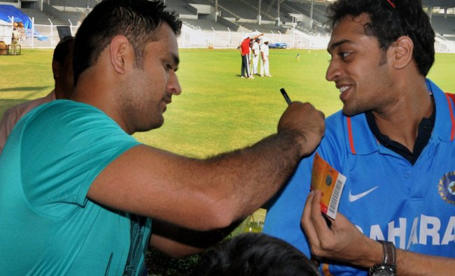 M S Dhoni signs autographs for his fans during a practice session at Braborne Stadium in Mumbai...