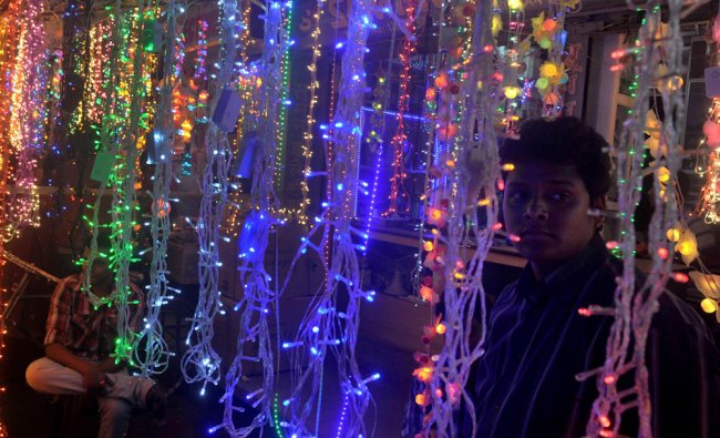 A vendor waits for customers as he sells electric lights ahead of Diwali in Siliguri ...