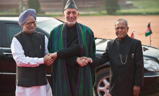Afghan President Hamid Karzai (C) shakes hands with Indian President Pranab Mukherjee...