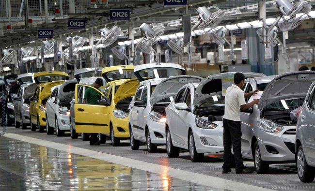 Workers assemble cars inside the Hyundai Motor India Ltd. plant at Kancheepuram district in the sout