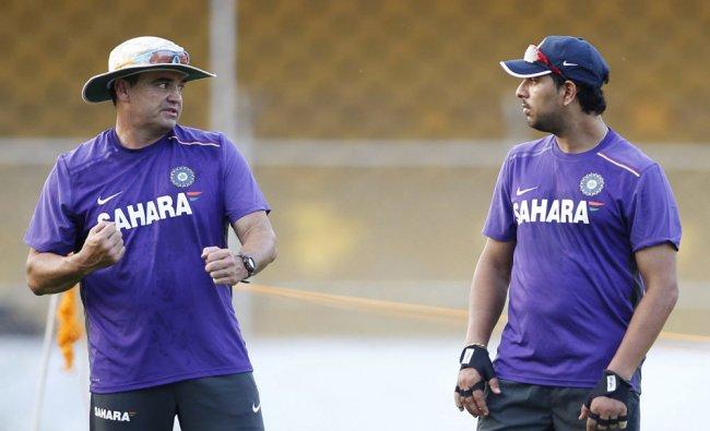Indian cricket team bowling coach Joe Dawes, left talks with Yuvraj Singh during a practice...