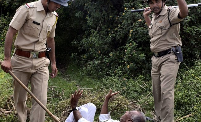 Police charge one of the activists of Swabhimani Shetkari Sanghatana during a protest at a...