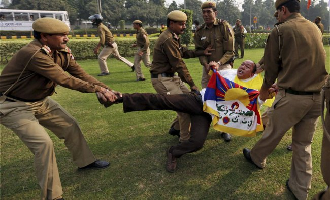 Policemen detain a Tibetan Youth Congress (TYC) supporter as he protests outside the Chinese...