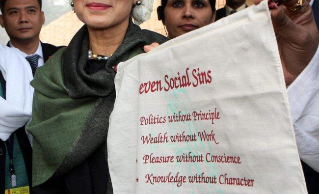 Aung San Suu Kyi receives a scroll bearing \'seven social sins\' quoted by Mahatma Gandhi