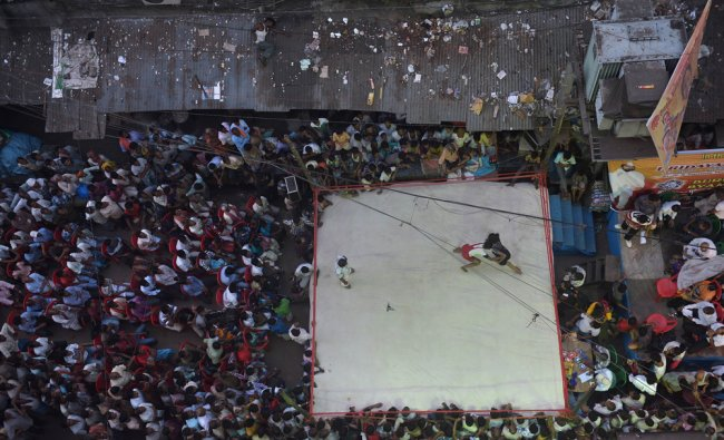 Spectators watch an outdoor local wrestling competition in Kolkata...