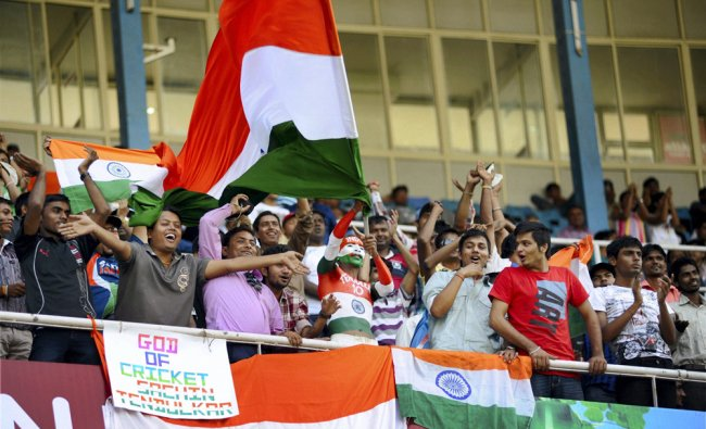 Fans wave the national flag on the opening day of the first cricket test between India and England