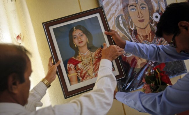 Father of Savita is helped by a family friend as he hangs her portrait