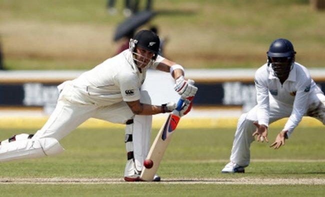 New Zealand\'s Brendon McCullum (L) plays a shot next to Sri Lanka\'s Tharanga Paranavitana...